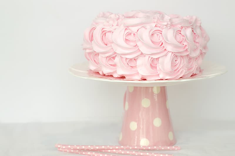 Pink icing coated cake on white and pink cake stand