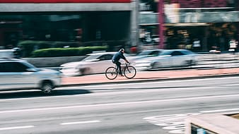 Selective focus photo of person riding on bicycle beside road